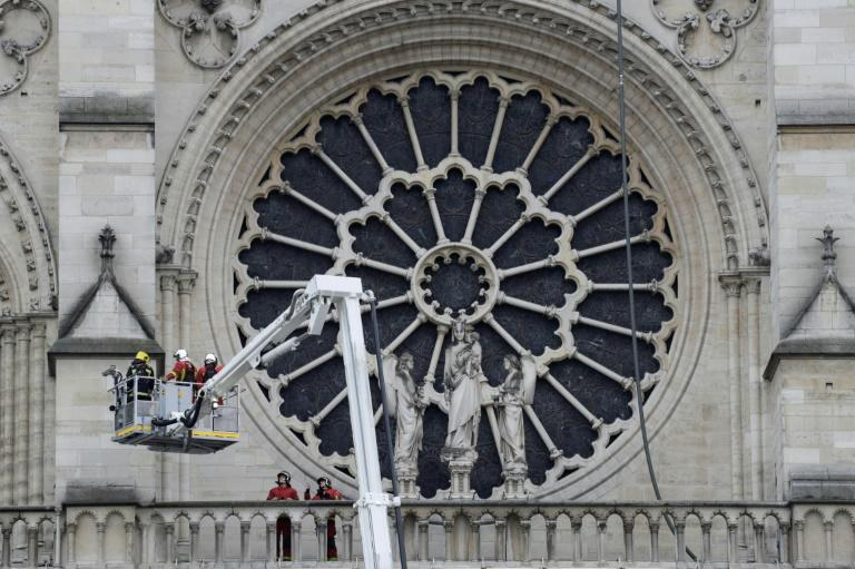 Firefighters outside the south transept Rose window. Experts say it could take decades to restore Notre-Dame Cathedral