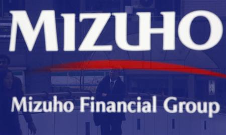 A man is reflected on an advertisement board of Mizuho Financial Group's Mizuho Bank in Tokyo