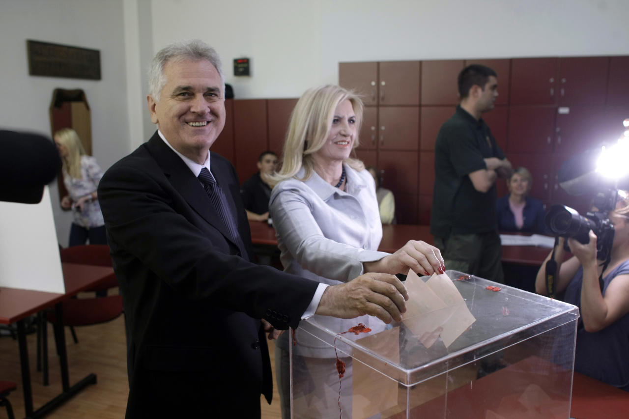 Tomislav Nikolic, left, the nationalist Serbian Progressive Party leader and presidential candidate, and his wife, Dragica, center, cast their ballots at the presidential runoff elections in Belgrade, Serbia, Sunday, May 20, 2012. Serbians voted Sunday in a presidential runoff election that pits pro European Union Boris Tadic against nationalist Tomislav Nikolic who wants closer ties with Russia and is threatening protests if he loses because of alleged ballot rigging. (AP Photo/ Marko Drobnjakovic)