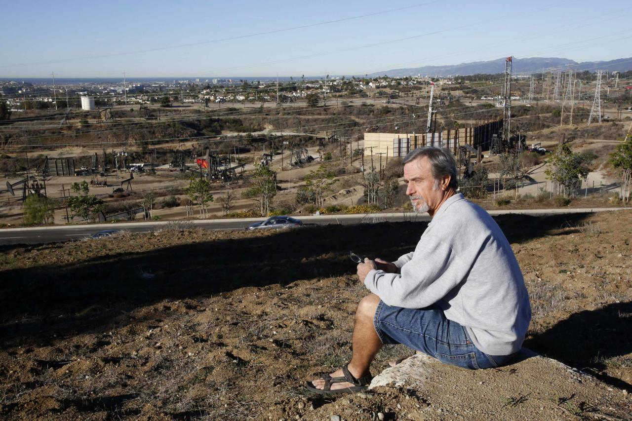 "Homeowner Gary Gless sits on a hill in his neighborhood overlooking drilling wells in Los Angeles, California December 11, 2013. The United States has a long history of keeping industrial activity out of middle and upper-middle-class residential neighborhoods. But that is starting to change with the spread of new technology for oil and gas drilling, such as horizontal drilling and hydraulic fracturing, or ""fracking."" Freeport-McMoRan, part of Freeport-McMoRan Copper & Gold Inc, said that, for the past three years, its surveys of the oilfield and surrounding communities have found no connection between its activities and ""localized claims of property damage."" It said it would continue to evaluate the issue. Picture taken December 11, 2013. To match Analysis FRACKING-HOMEOWNERS/ REUTERS/Mario Anzuoni (UNITED STATES - Tags: ENERGY BUSINESS REAL ESTATE)"