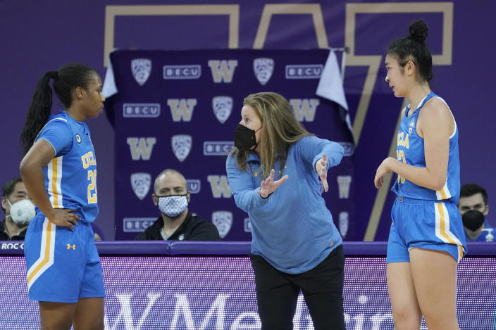 UCLA head coach Cori Close, center, talks with guard Charisma Osborne, left, and guard Natalie Chou, right, during the second half of an NCAA college basketball game against Washington, Sunday, Feb. 7, 2021, in Seattle. (AP Photo/Ted S. Warren)
