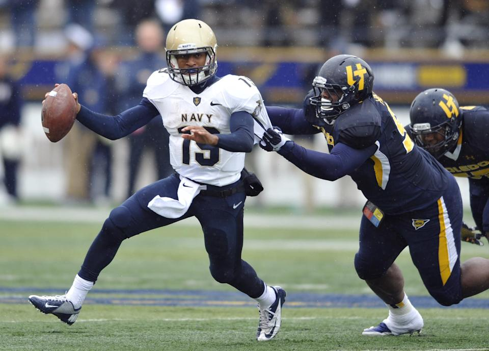 Toledo defensive tackle Treyvon Hester, right, chases Navy quarterback Keenan Reynolds in the first quarter of an NCAA college football game in Toledo, Ohio, Saturday, Oct. 19, 2013. (AP Photo/David Richard)