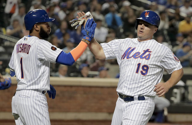 New York Mets' Jay Bruce (19) is congratulated by Amed Rosario (1) after scoring on a sacrifice fly by Noah Syndergaard against the Toronto Blue Jays during the fourth inning of a baseball game, Tuesday, May 15, 2018, in New York. (AP Photo/Julie Jacobson)