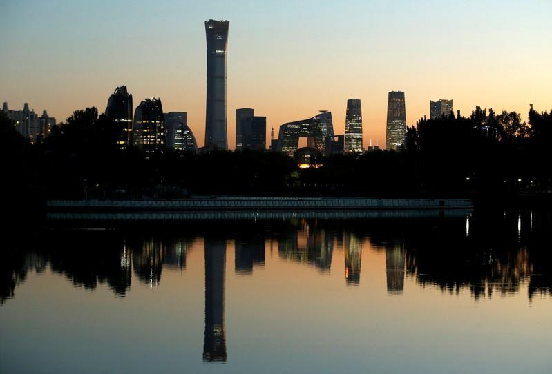 The cityscape of the Beijing Central Business District is reflected in a pond during sunset
