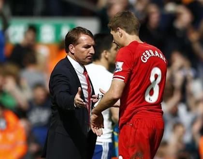 Liverpool's Steven Gerrard (R) is greeted by manager Brendan Rodgers as he leaves the pitch following their English Premier League soccer match against Chelsea at Anfield in Liverpool, northern England April 27, 2014. REUTERS/Darren Staples
