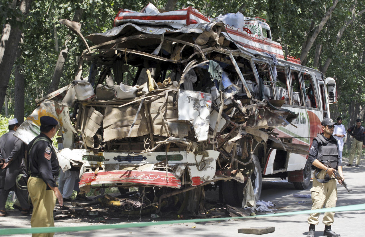 Pakistani policemen stand by the wreckage of a bus that exploded when a bomb planted in it went off on the outskirts of Peshawar, Pakistan, Friday, June 8, 2012. A bomb tore through a bus carrying government employees and other civilians in northwestern Pakistan killing several people in an attack that served as a reminder of the continued militant threat despite a significant drop in violence over the past year, officials said. (AP Photo/Mohammad Sajjad)