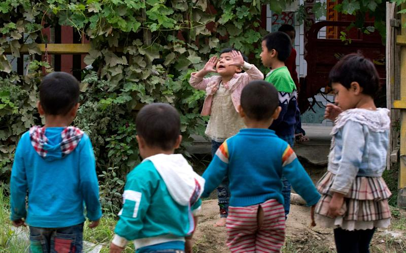 Uighur children play outdoors in Hotan, in western China's Xinjiang region - AP