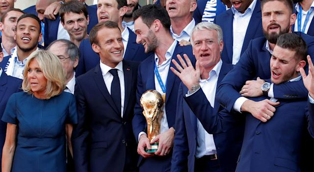 French President Emmanuel Macron and his wife Brigitte Macron pose with France soccer team captain Hugo Lloris holding the trophy, coach Didier Deschamps and players before a reception to honour the France soccer team after their victory in the 2018 Russia Soccer World Cup, at the Elysee Palace in Paris, France, July 16, 2018. REUTERS/Philippe Wojazer TPX IMAGES OF THE DAY