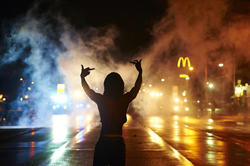 A protester gestures angrily at cops as tear gas fills the streets of Ferguson after curfew early Sunday, Aug. 17, 2014. (James Keivom/New York Daily News via Getty Images)