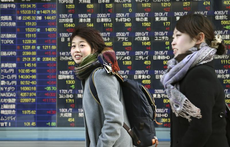 People walk by an electronic stock board of a securities firm in Tokyo, Thursday, March 6, 2014. Shares were mostly higher in Asia on Thursday as the standoff over Ukraine between Russia and the West continued to ease and the yen weakened. (AP Photo/Koji Sasahara)