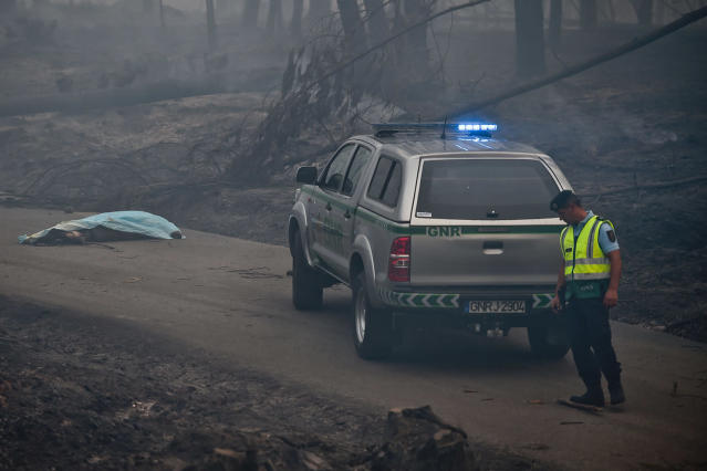 <p>A policeman stands by a dead body of a victim of a wildfire in Pedrogao, on June 18, 2017. At least 62 people have been killed in forest fires in central Portugal, many of them trapped in their cars as flames swept over a road Saturday evening. (Patricia De Melo Moreira/AFP/Getty Images) </p>