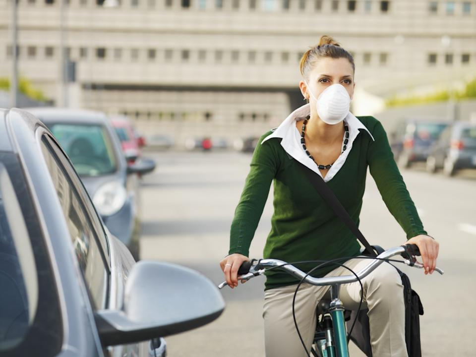 woman with dust mask commuting on bicycle