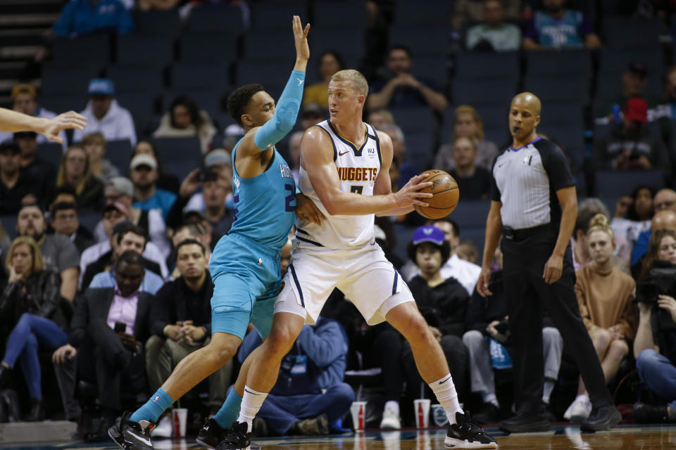 Denver Nuggets forward Mason Plumlee, right, looks to pass against Charlotte Hornets forward P.J. Washington during the first half of an NBA basketball game in Charlotte, N.C., Thursday, March 5, 2020. (AP Photo/Nell Redmond)