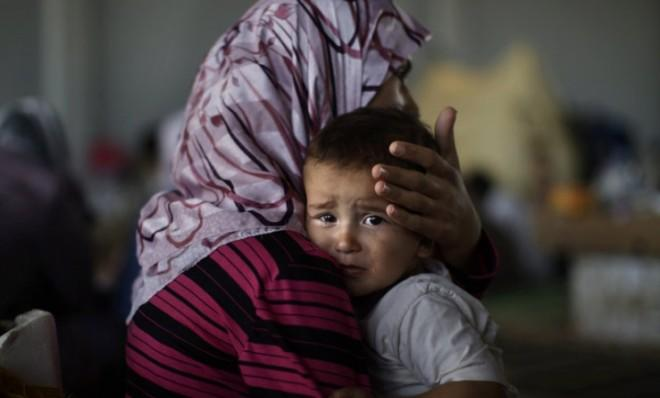 Little Amjad Al-Saleh, whose family fled their home in September, is comforted by his mother after suffering food poisoning.