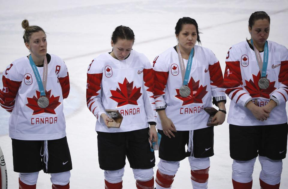 Jocelyne Larocque (second from right) holds her silver medal in her hand, next to teammates wearing their medals during the medal ceremony. (REUTERS/Brian Snyder)