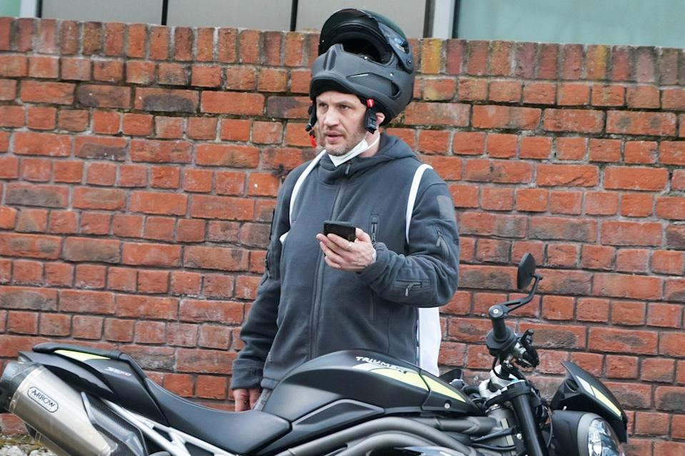 <p>Tom Hardy is spotted wearing a sturdy helmet beside his motorcycle on Sunday in London. </p>