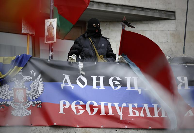 "A masked pro-Russian activist looks from a balcony of the regional administration building decorated with a banner reading ""Donetsk Republic"" in Donetsk, Ukraine, Saturday, April 12, 2014. The unrest in Donetsk and Slovyansk, about 90 kilometers (55 miles) to the north, were the latest shows of spiraling anger in eastern Ukraine, which has a large Russian-speaking population and was also the support base for Viktor Yanukovych, the Ukrainian president who was ousted in February after months of protests in the capital, Kiev.(AP Photo/Max Vetrov)"