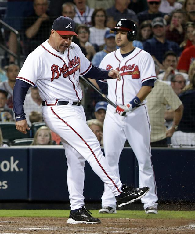 Atlanta Braves manager Fredi Gonzalez, left, kicks dirt on home plate after being ejected by umpire Angel Hernandez in the seventh inning of a baseball game against the Milwaukee Brewers, Monday, Sept. 23, 2013, in Atlanta. (AP Photo/David Goldman)