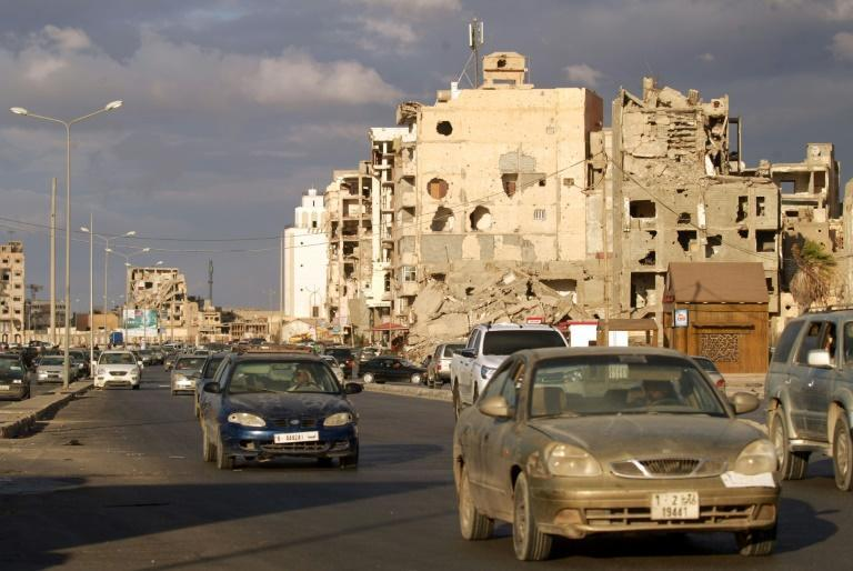 Cars drive near shell-pocked buildings in Libya's eastern coastal city of Benghazi on October 23, 2020, after a ceasefire agreement was signed between the country's warring factions