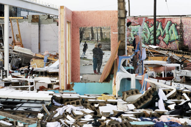 People are reflected in a mirror of a building destroyed by storms Tuesday, March 3, 2020, in Nashville, Tenn. Tornadoes ripped across Tennessee early Tuesday, shredding buildings and killing multiple people. (AP Photo/Mark Humphrey)