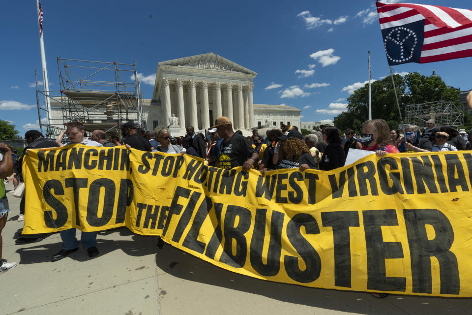 """Protesters hold banners as they march from the U.S. Supreme Court, to the Hart Senate Office building in Washington, Wednesday, June 23, 2021, announcing a """"Moral March on Manchin and McConnell"""" and highlighting the right to vote and living wages. (AP Photo/Manuel Balce Ceneta)"""