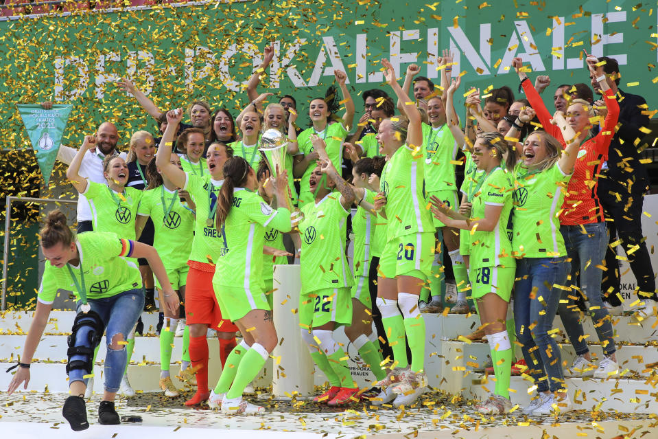 Wolfsburg's players celebrate during the award ceremony after their victory against Frankfurt, during their German Women's DFB Cup Final match, in Cologne, Germany, Sunday May, 30, 2021. (Marcel Kusch/dpa via AP)