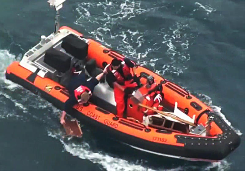 In this image taken from U.S. Coast Guard video, a rescuer retrieves a piece of debris from the ocean off the Baja California, Mexico coast near Ensenada Sunday, April 29, 2012. The 37-foot racing sailboat Aegean, carrying a crew of four, was reported missing Saturday, the U.S. Coast Guard said. The yacht appeared to have collided at night with a much larger vessel, leaving three crew members dead and one missing. (AP Photo/USCG Petty Officer Third Class Seth Johnson)
