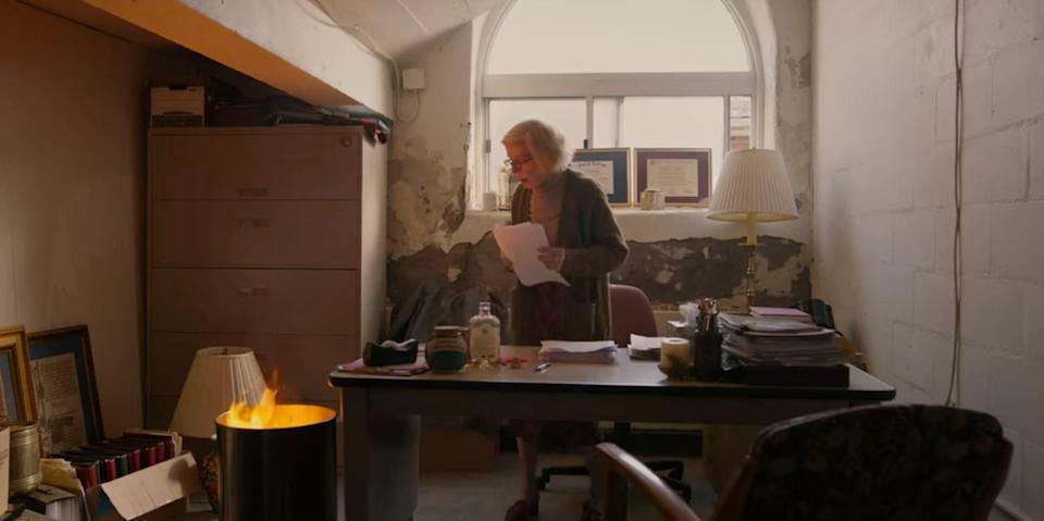 Joan stares at trash can fire