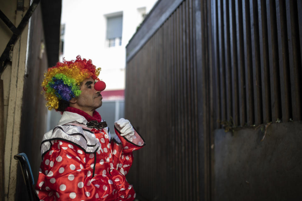 Belhussein Abdelsalam, a Charlie Chaplin impersonator puts on a clown outfit in a flower shop before performing, in Rabat, Morocco, Thursday, Dec. 31, 2020. When 58-year-old Moroccan Belhussein Abdelsalam was arrested and lost his job three decades ago, he saw Charlie Chaplin on television and in that moment decided upon a new career: impersonating the British actor and silent movie maker remembered for his Little Tramp character. (AP Photo/Mosa'ab Elshamy)