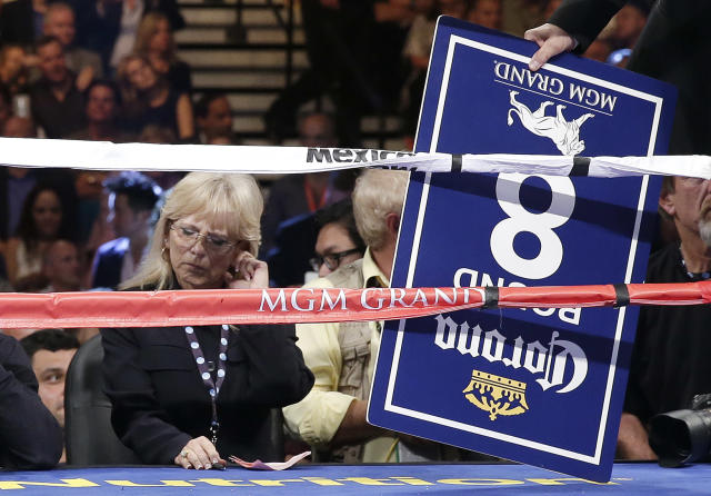 In this photo taken Saturday, Sept. 14, 2012, boxing judge Cynthia C.J. Ross, left, waits to hand her scorecard to the referee after the seventh round of the fight between Canelo Alvarez and Floyd Mayweather Jr. in Las Vegas. Ross is temporarily stepping away from the ring after drawing widespread criticism for scoring the fight a draw when two other judges scored Mayweather the clear winner. (AP Photo/Eric Jamison)