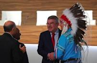 Thomas Bach, President of the International Olympic Committee (IOC), shakes hands with Wilton Littlechild, an observer of the 133rd IOC session, as they talk to other attendants in Buenos Aires, Argentina October 9, 2018. REUTERS/Marcos Brindicci
