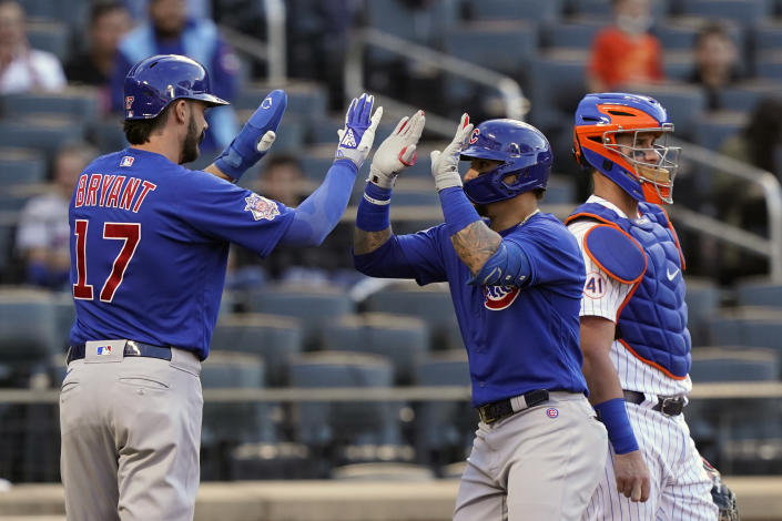 Chicago Cubs' Kris Bryant (17) greets Javier Baez at the plate after scoring on Baez's home run in the first inning of the team's baseball game against the New York Mets, Thursday, June 17, 2021, in New York. Mets catcher James McCann is at right. (AP Photo/Kathy Willens)