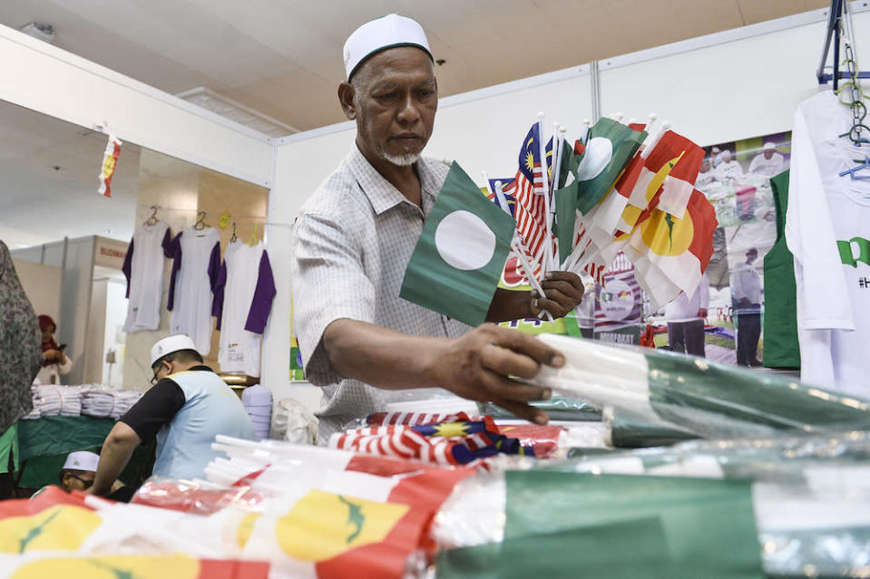 A man is pictured selling PAS-Umno flags at the Putra World Trade Centre in Kuala Lumpur September 13, 2019. — Picture by Miera Zulyana