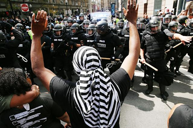 <p>Protesters face off with riot police escorting conservative activists following a march in Boston against a planned 'Free Speech Rally' just one week after the violent 'Unite the Right' rally in Virginia left one woman dead and dozens more injured on August 19, 2017 in Boston, Mass. (Photo: Spencer Platt/Getty Images) </p>