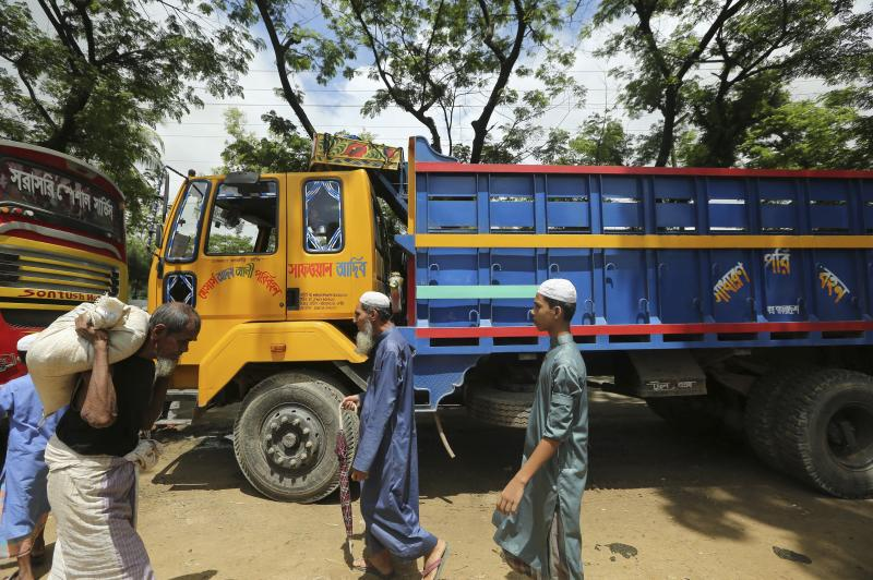 Rohingya refugees walk past trucks that were brought to take them to the Myanmar border outside Nayapara Rohingya refugee camp in Cox's Bazar, Bangladesh, Thursday, Aug.22, 2019. Bangladesh's refugee commissioner said Thursday that no Rohingya Muslims turned up to return to Myanmar from camps in the South Asian nation. (AP Photo/Mahmud Hossain Opu)