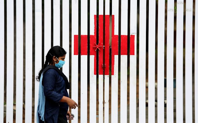 An Indian walks in front of the 'Red Cross' symbol painted on a fence during an extended lockdown over suspected coronavirus disease (COVID-19) cases in Bangalore, India - JAGADEESH NV/EPA-EFE/Shutterstock