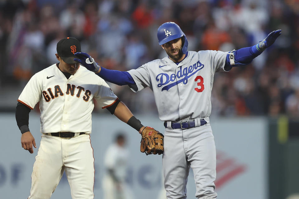 Los Angeles Dodgers' Chris Taylor (3) gestures next to San Francisco Giants' Donovan Solano after hitting a double during the second inning of Game 2 of a baseball National League Division Series Saturday, Oct. 9, 2021, in San Francisco. (AP Photo/John Hefti)