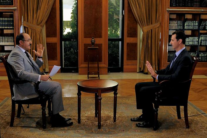In this photo, which AP obtained from Syrian official news agency SANA and which has been authenticated based on its contents and other AP reporting, President Bashar Assad, right, gestures as he speaks during an interview with Lebanon's Al-Mayadeen TV, at the presidential palace in Damascus, Syria, Monday, Oct. 21, 2013. Syria's president said Monday that the factors that would allow a landmark conference aimed at ending the country's civil war do not yet exist, throwing further doubt on international efforts to hold peace talks that have already been repeatedly delayed. (AP Photo/SANA)