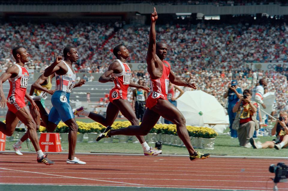Jamaican-born Canadian Ben Johnson (C) crosses the finish line to win the Olympic 100m final in a world record 9.79 seconds on September 24, 1988 at Seoul Olympic Stadium. Carl Lewis from USA (l) took second place. Johnson, nicknamed as
