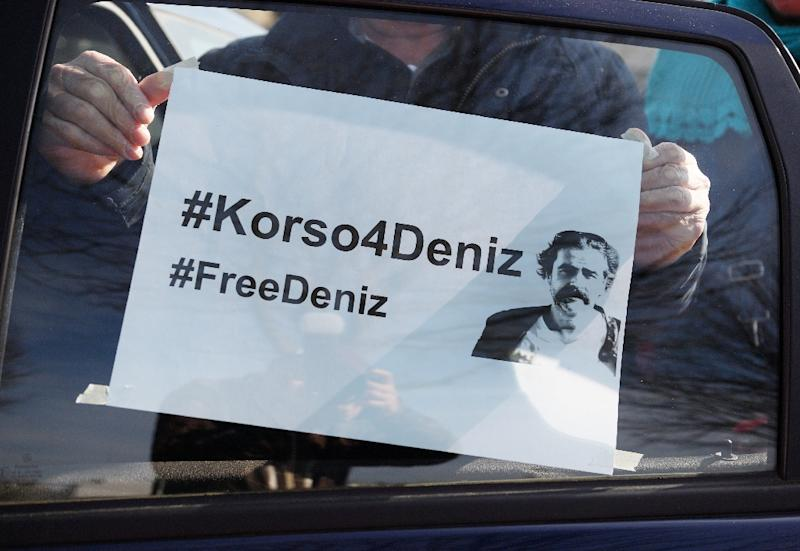 "A demonstrator sticks a poster reading ""#FreeDeniz"" on a car window as he takes part on February 25, 2017 in Floersheim near Frankfurt am Main, western Germany, in a protest to support journalist Deniz Yucel detained in Turkey"