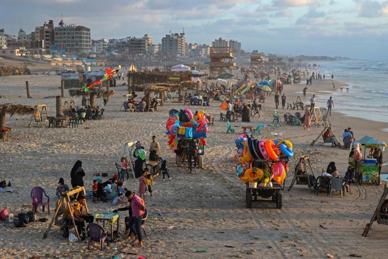 Palestinians gather at the beach in Gaza City on May 22, 2021, following a ceasefire that ended 11 days of relentless Israeli air strikes on the besieged coastal enclave