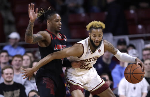 Louisville guard Khwan Fore, left, tries to hold back Boston College guard Ky Bowman, right, during the first half of an NCAA college basketball game in Boston, Wednesday, Feb. 27, 2019. (AP Photo/Charles Krupa)