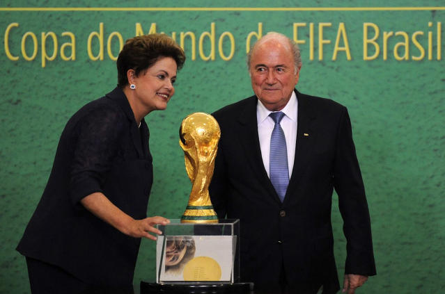 Brazilian President Dilma Roussef (L) and FIFA President Joseph Blatter stand next to FIFA World Cup trophy during its presentation in Brasilia on June 2, 2014 (AFP Photo/Jose Cruz)