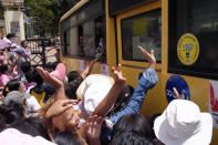A crowd waves to people onboard a bus that drove out of Insein prison in Yangon, Myanmar Saturday, April 17, 2021. Myanmar's junta on Saturday announced it pardoned and released more than 23,000 prisoners to mark the new year holiday, but it wasn't immediately clear if they included pro-democracy activists who were detained in the wake of the February coup. (AP Photo)