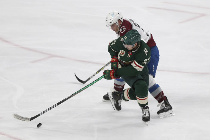 Minnesota Wild's Kevin Fiala (22) and Colorado Avalanche's Jacob MacDonald (34) go after the puck during the third period of an NHL hockey game Wednesday, April 7, 2021, in St. Paul, Minn. (AP Photo/Stacy Bengs)
