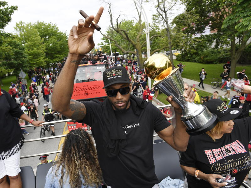 Toronto Raptors forward Kawhi Leonard greets fans while holding his playoffs MVP trophy during the 2019 Toronto Raptors NBA basketball championship parade in Toronto, Monday, June 17, 2019. (Frank Gunn/The Canadian Press via AP)