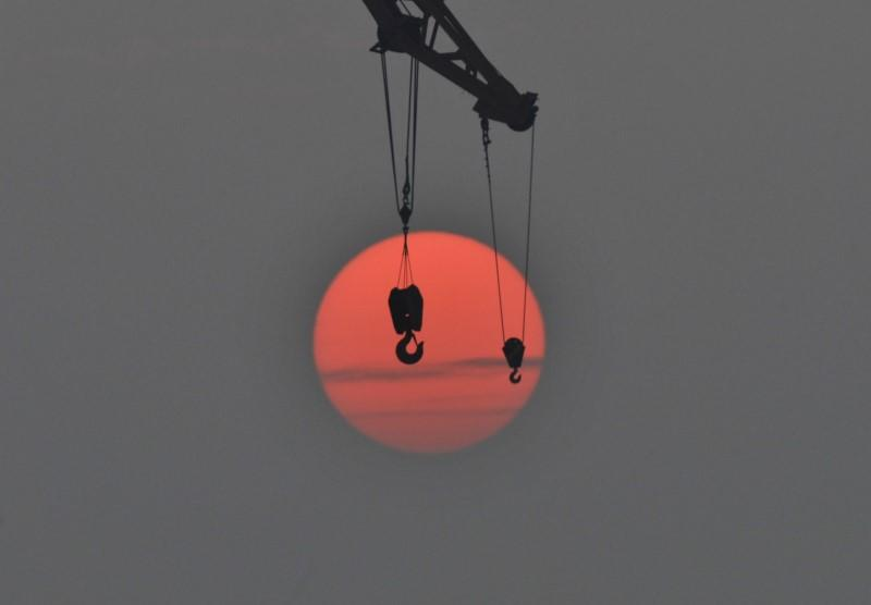 The hooks of a crane are pictured in front of the setting sun in Qingdao