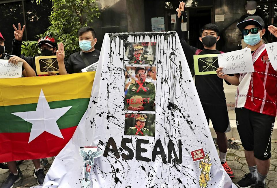 People raise three fingers near a display of paint-spattered photos of three men in uniform and the words Reject and ASEAN