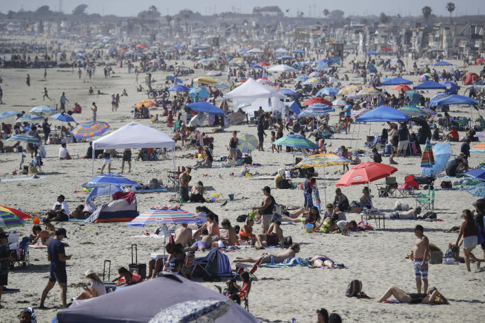 FILE - In this May 24, 2020, file photo, visitors gather on the beach in Newport Beach, Calif., during the coronavirus outbreak. Warm weather beach destinations are the most popular vacation searches, with Florida, Myrtle Beach, San Diego and Key West among the top considerations. (AP Photo/Marcio Jose Sanchez, File)