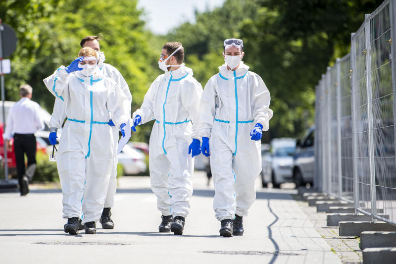 21 June 2020, North Rhine-Westphalia, Verl: Bundeswehr soldiers in protective suits and wearing mouth-and-nose masks go to the homes to test more people for the coronavirus. Following positive corona tests, the city of Verl has set up a quarantine for numerous Tönnies employees in the Sürenheide district. Several apartment buildings in which Tönnies' contract workers live have been quarantined. A total of almost 670 people live in the three streets affected. Photo: David Inderlied/dpa (Photo by David Inderlied/picture alliance via Getty Images)